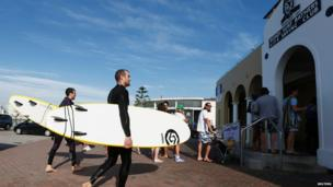 Two surfers walk past residents as they line up to vote