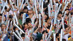 People celebrate waving plastic banners which say 'Discover tomorrow'