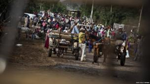 Crowd of people with horses and carts