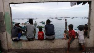 A group of people look out to the coast where fellow evacuees wait on boats