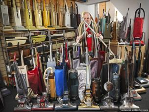 A man stood among a collection of vacuum cleaners.