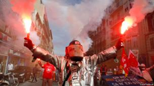 Steelworkers in Marseille burn flares