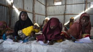 Ismahan, 13, attends a math class while taking care of her three-year-old sister in Mogadishu, Somalia - 8 September 2013