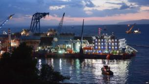 In the early hours of the morning, a pink sky breaks through blue clouds overlooking the salvage attempt of the Costa Concordia which is lit up by many lights on the equipment.