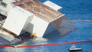 Giant metal chains attached to equipment can be seen in order to help get the ship upright.