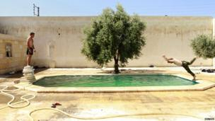 A Free Syrian Army fighter dives into a swimming pool, as his fellow fighter watches him in Aleppo.