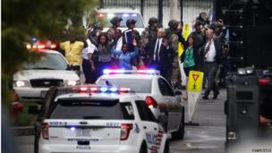 People come out from a building with their hands up after a shooting happened at the Washington Navy Yard (16 September 2013)