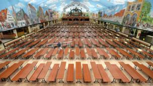 """A man walks through the empty Hacker Pschorr beer tent during preparations for the 180th Oktoberfest beer festival in Munich, southern Germany, on Monday, Sept. 16, 2013. The world""""s largest beer festival will be held from Sept. 21 to Oct. 6, 2013 and will be attended by millions of visitors."""