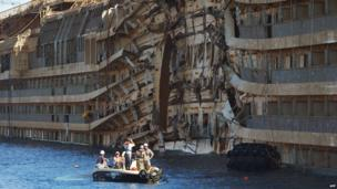 Salvage workers photograph parts of the Costa Concordia