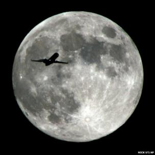 An aircraft approaching Los Angeles International Airport crosses the moon