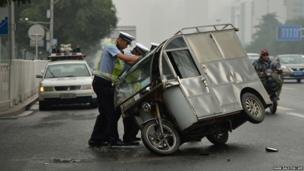 Chinese police help a motorcycle taxi driver right his vehicle after a collision with a car in Beijing