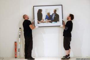 Gallery assistants hang an artwork by Alison Jackson
