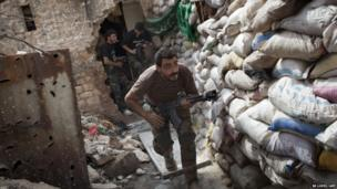 Rebel fighters duck as they run behind a barricade to avoid being fired at by Syrian regime forces in Aleppo