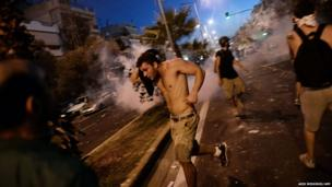 Protesters run away from police during clashes in the western Athens