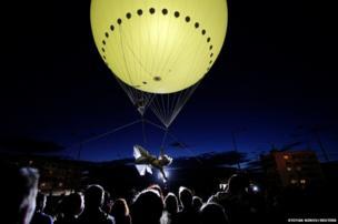 An artist descends from a balloon