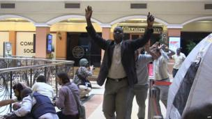 Shoppers raise their arms as they are evacuated from the Westgate mall (21 Sept. 2013) (screengrab)