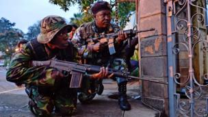 Kenyan soldiers take cover after heavy gunfire near Westgate mall in Nairobi (23 September 2013)