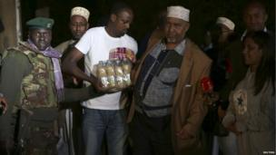 Members of Nairobi's Somali community deliver food and drinks to soldiers and security personnel near the shopping centre as darkness falls on Monday September 23.