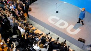 Chancellor Angela Merkel enters the stage after at her party's headquarters in Berlin