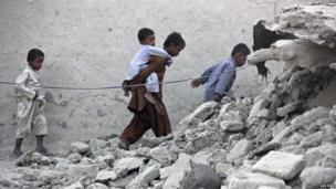 Survivors of an earthquake walk on rubble of a mud house after it collapsed following the quake in the town of Awaran