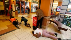 People scramble for safety as armed police search the Westgate shopping centre in Nairobi