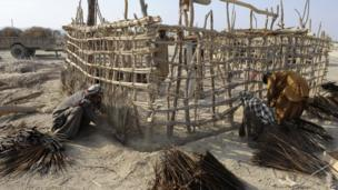 Pakistani earthquake survivors prepare temporary huts for their family near their collapsed mud houses in the Dhall Bedi Peerander area of the earthquake-devastated district of Awaran on 27 September 2013
