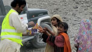 A Pakistani volunteer distributes biscuit to earthquake survivors
