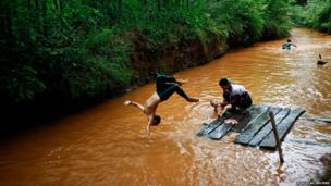 An ethnic Pa-O boy dives into the stream while his mother bathes a baby near Inle lake in Shan state, one of the main tourist attractions in Burma (also known as Myanmar).