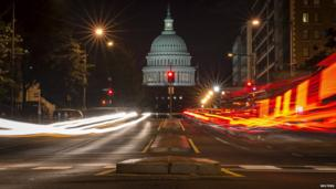 A red traffic light stands in front of the US Capitol building in Washington 30 September, 2013, approximately one hour before the US federal government partially shut down after lawmakers failed to compromise on an emergency spending bill.