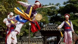 """A traditional South Korean dancer flips through the air while performing during the """"Taste Korea! Korean Royal Cuisine Festival"""" held at Unhyeon Palace, also known as Unhyeongung Royal Residence, in Seoul, South Korea, on Tuesday, 1 October 2013."""