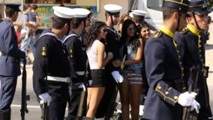 Girls pose for a picture with Cypriot navy personnel during the ceremony marking Cyprus' independence from British colonial rule on 1 October, 2013 in the capital Nicosia.