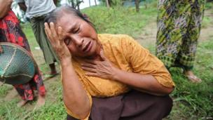A Muslim woman reacts after her house was burned down