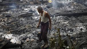 A Muslim man searches for his belongings left behind of his burnt home