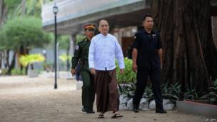 Myanmar President Thein Sein (C) comes out from a government guest house after a meeting with community representatives
