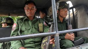 Myanmar soldiers sit on an convoy