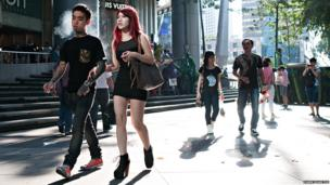 A young couple with tattoos, walk in front of a building
