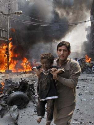 A man carries a child away from the site of a a car bomb in Peshawar, Pakistan