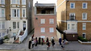 Artist Alex Chinneck's sliding house in Margate