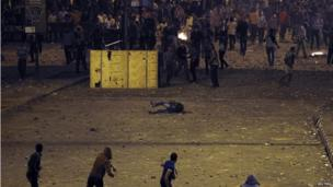 A man falls during clashes between anti- and pro-Morsi protesters in Cairo