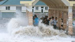 People dodge as a storm surge hits the coastline under the influence of Typhoon Fitow in Wenling, Zhejiang province, 6 October 2013