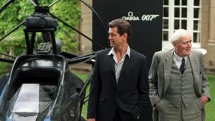 Actor Pierce Brosnan (L) poses for a photograph with Desmond Llewelyn