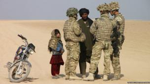 Two soldiers and an interpreter from the Queen's Royal Lancers speak to an Afghan motorcyclist and his daughter in Northern Helmand