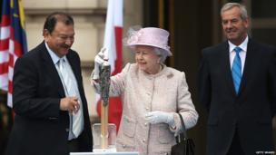 The Queen places her message inside the baton