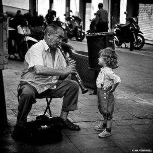 Man playing clarinet to a child in Spain