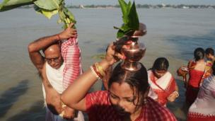 Indian Hindu devotees perform rituals with a banana tree wrapped in a sari, symbolising the wife of Hindu god Ganesha, near the river Ganges during the Durga Puja festival in Kolkata.