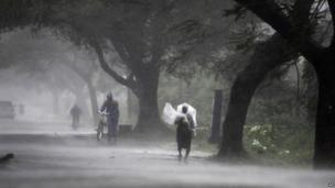 A man covers himself with a plastic sheet as a shield from the rain as he walks to a safer place near Gopalpur junction in Ganjam district