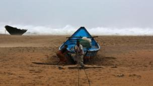Fishermen tie their boat along the shore at Donkuru village in Srikakulam district, in the southern Indian state of Andhra Pradesh on 12 October 2012.