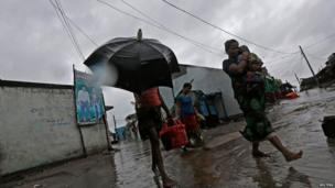 A woman carries her baby as she moves to a safer place with others at the village Donkuru in Srikakulam district in Andhra Pradesh state.