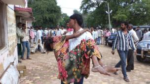 An Indian man carries a Hindu devotee injured in a stampede outside the Ratangarh Temple