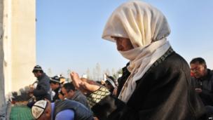 A Kyrgyz woman praying alongside a group of men in Bishkek, Kyrgyzstan.